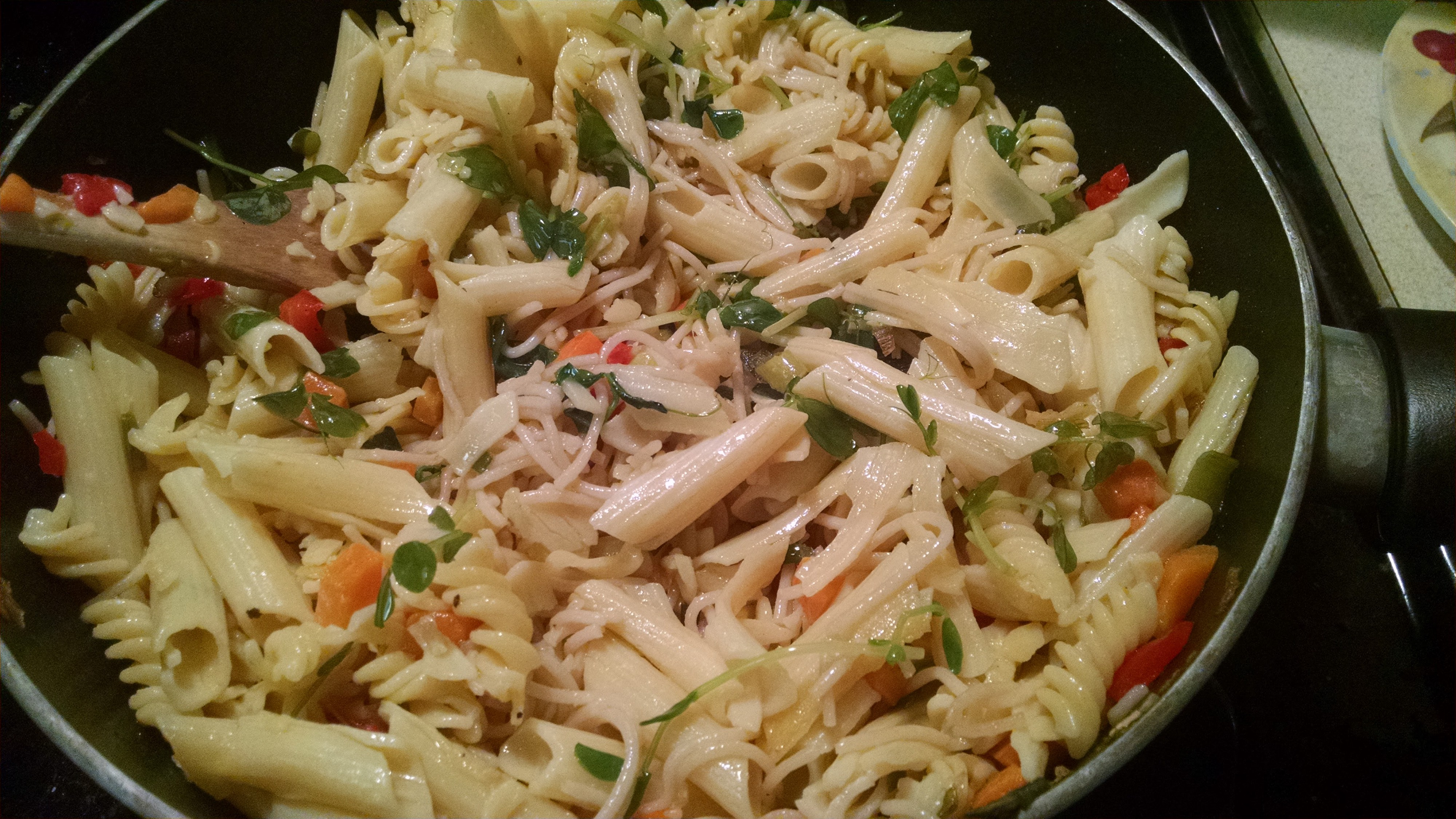 Photo of pasta and vegetables mixed together and cooking in a pan.