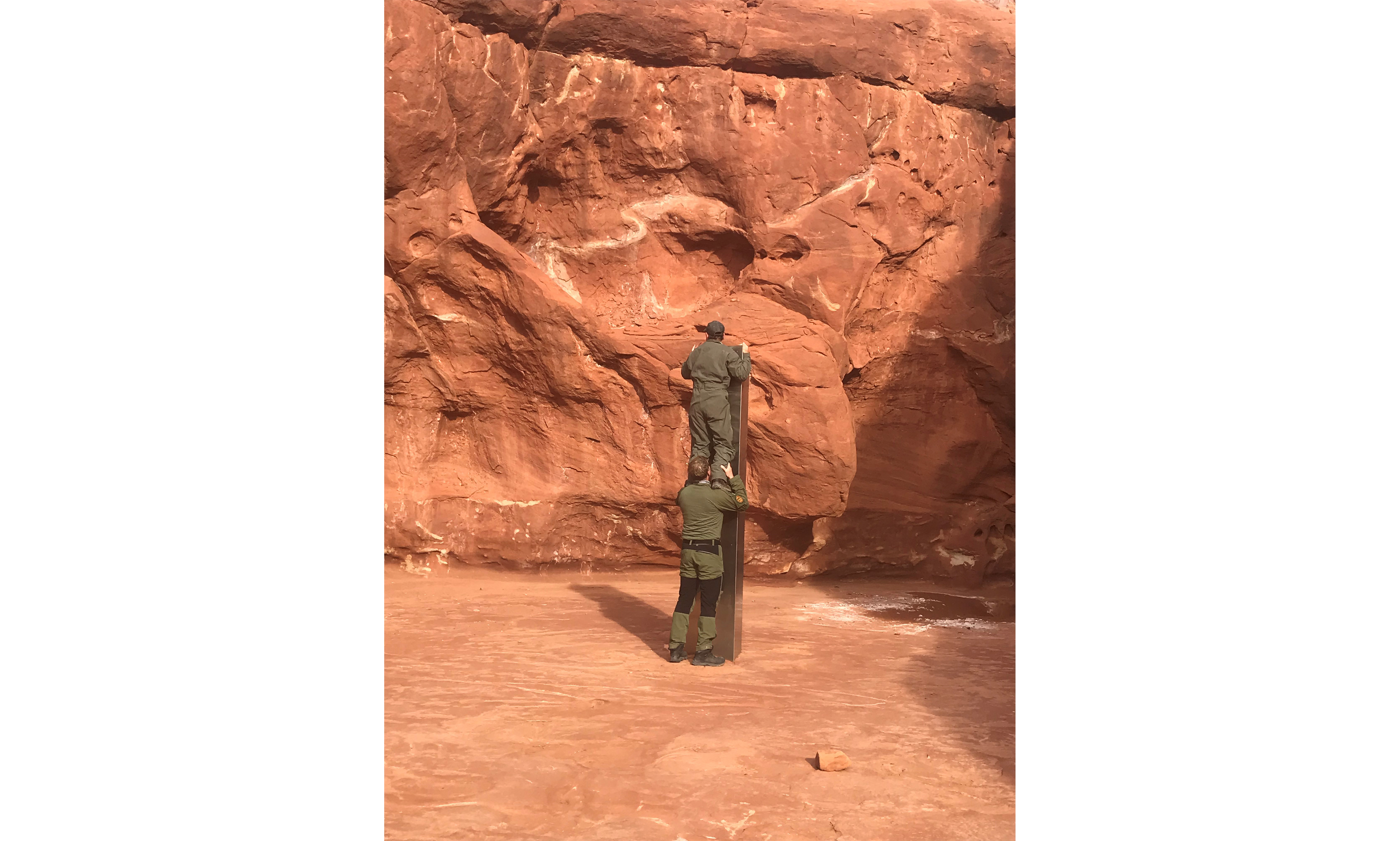 Two men examine the utah monolith, one standing on the other's shoulders.