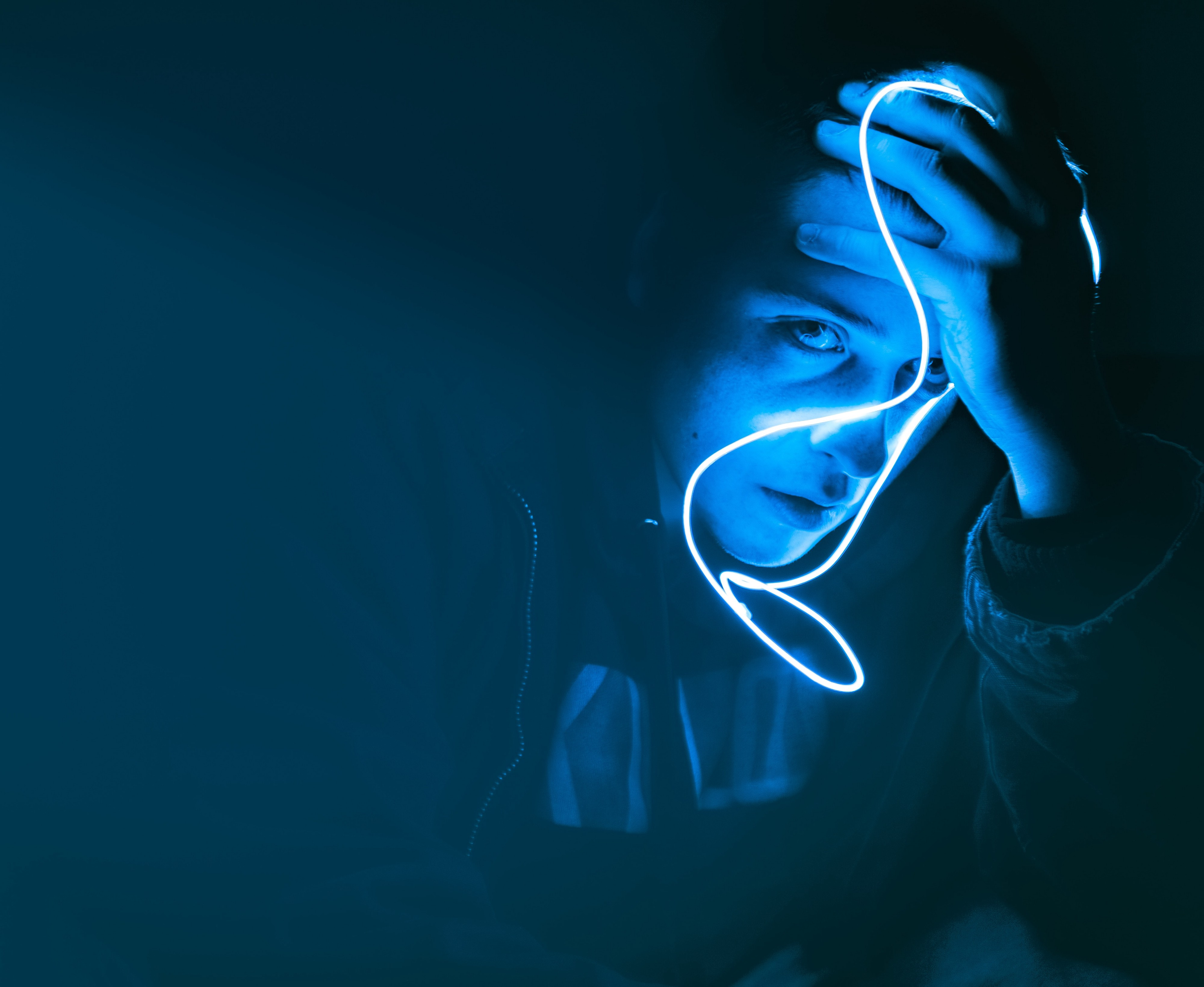 Person in a dark background with a cobalt blue light on their face, looking despondently at the camera.
