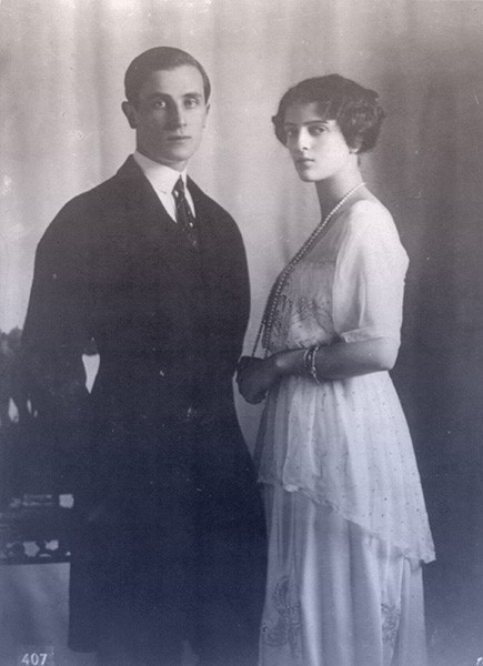 Felix and Irina standing together. He's in a dark suit with short, slicked-back hair. She's in a white day dress with pearls.