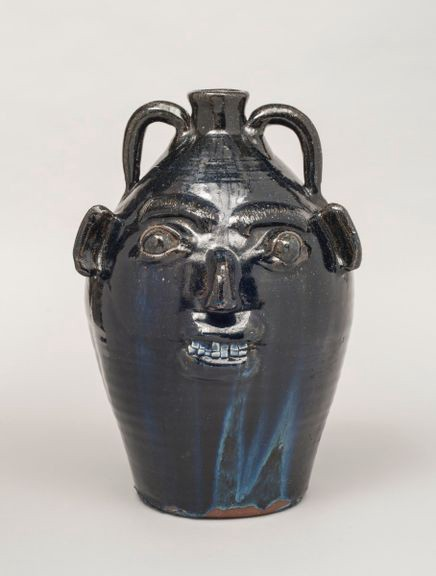 Black and blue face jug with a small toothy smile.