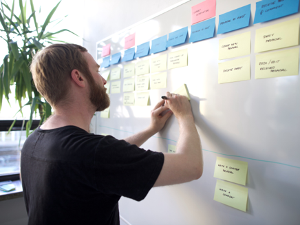A bearded man writing post-its on a wall to create a user story map.