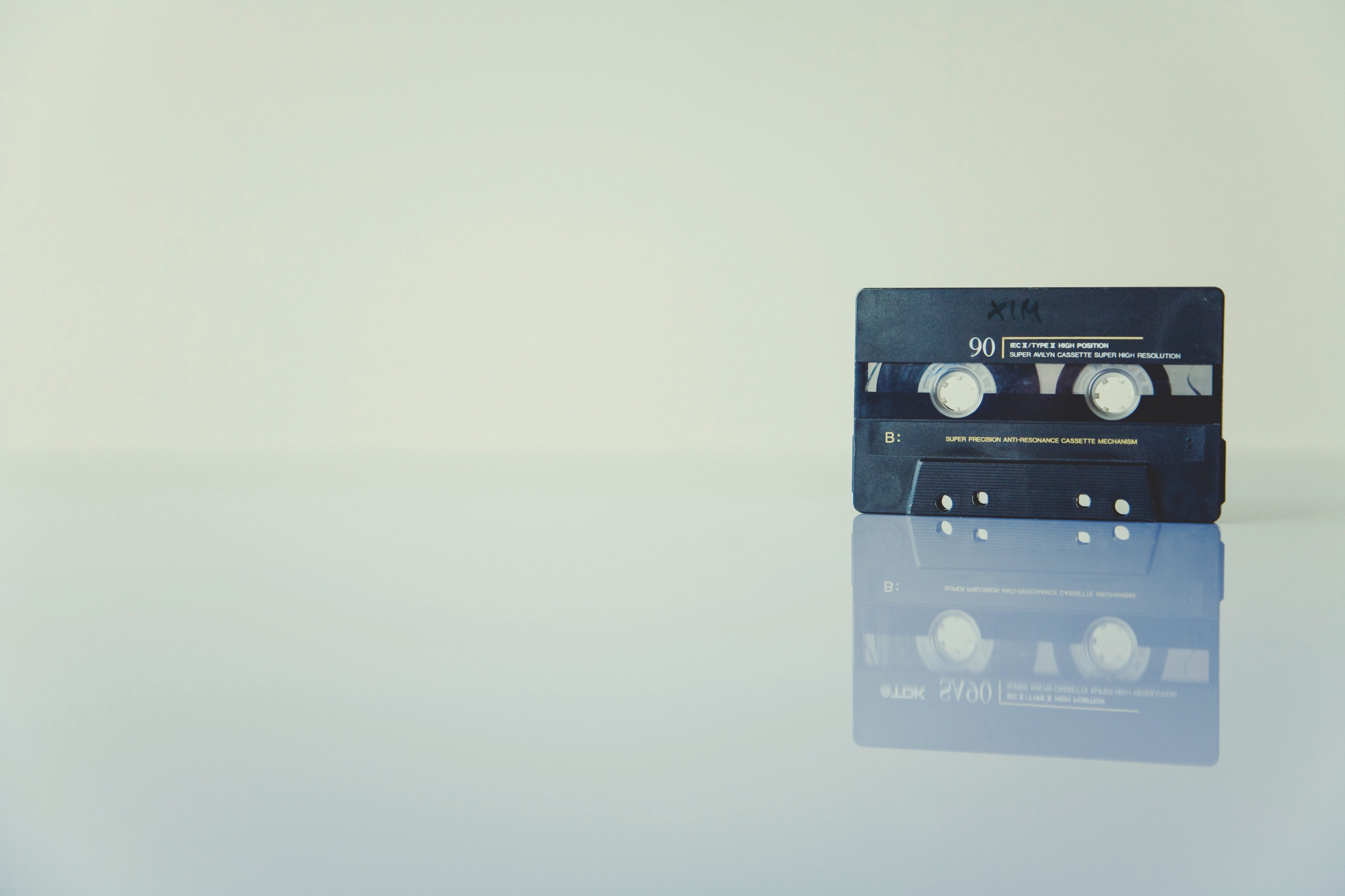 A dark cassette tape standing on a shiny tabletop.