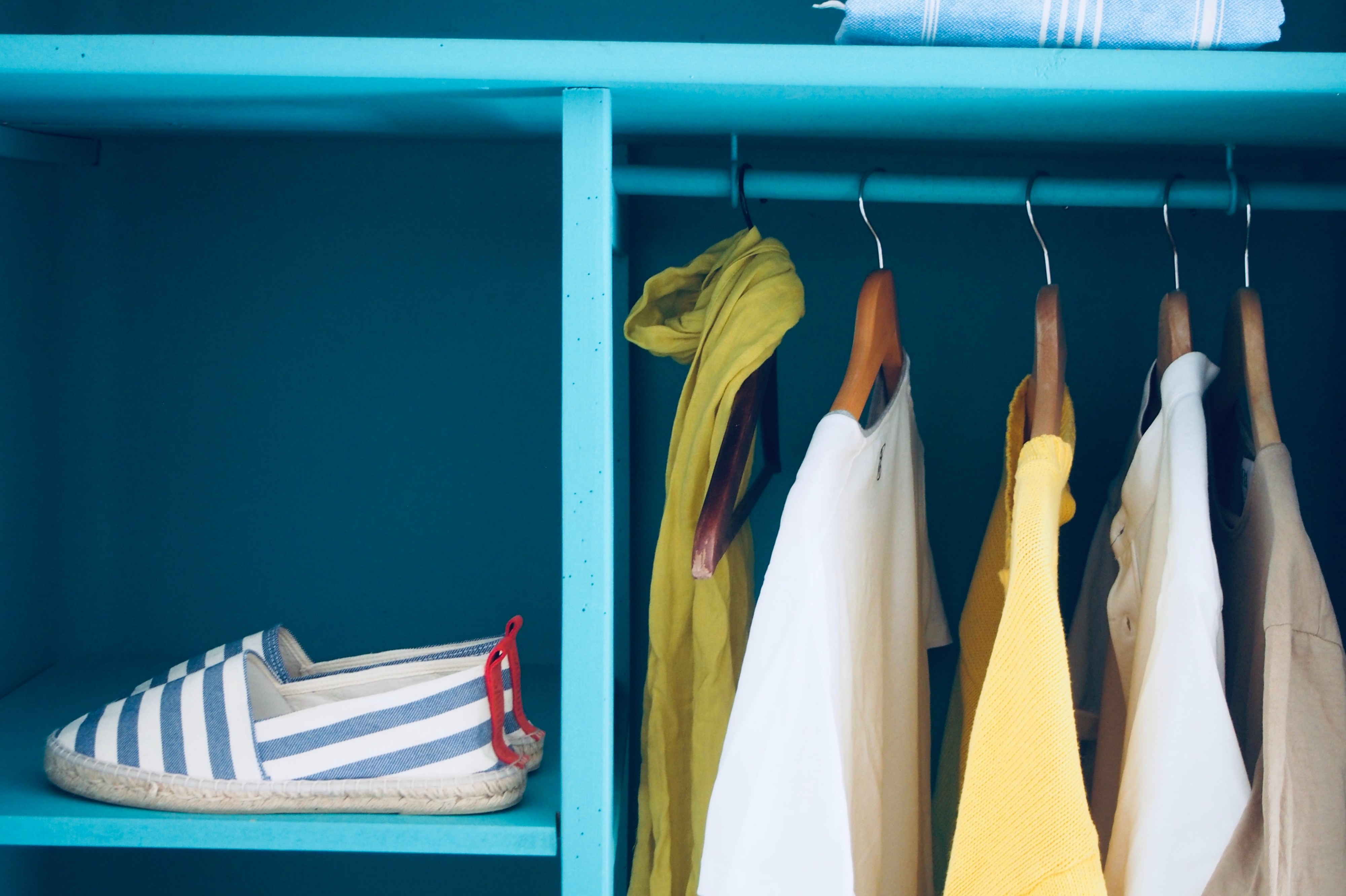 Clothing hanging neatly in a closet.