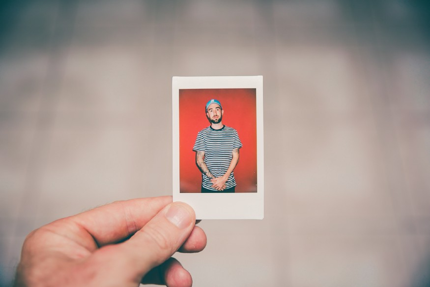 small photograph being held in front of camera
