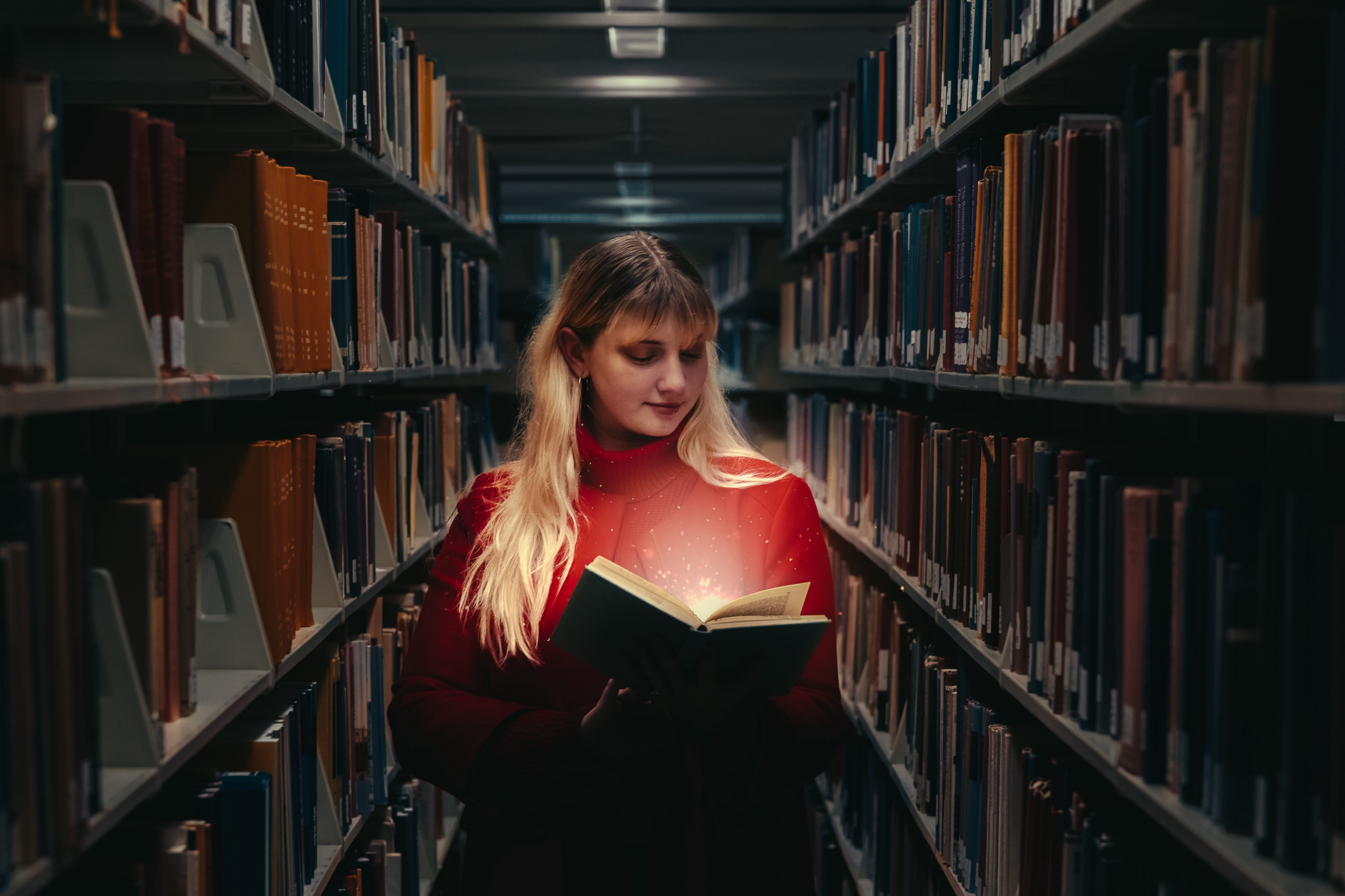 A woman holding a book, wearing a red turtleneck standing between two bookcases in a dark library. Light emanates from book.