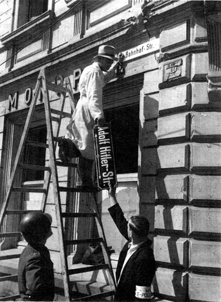 Worker removing Adolf Hitler street sign after World War II