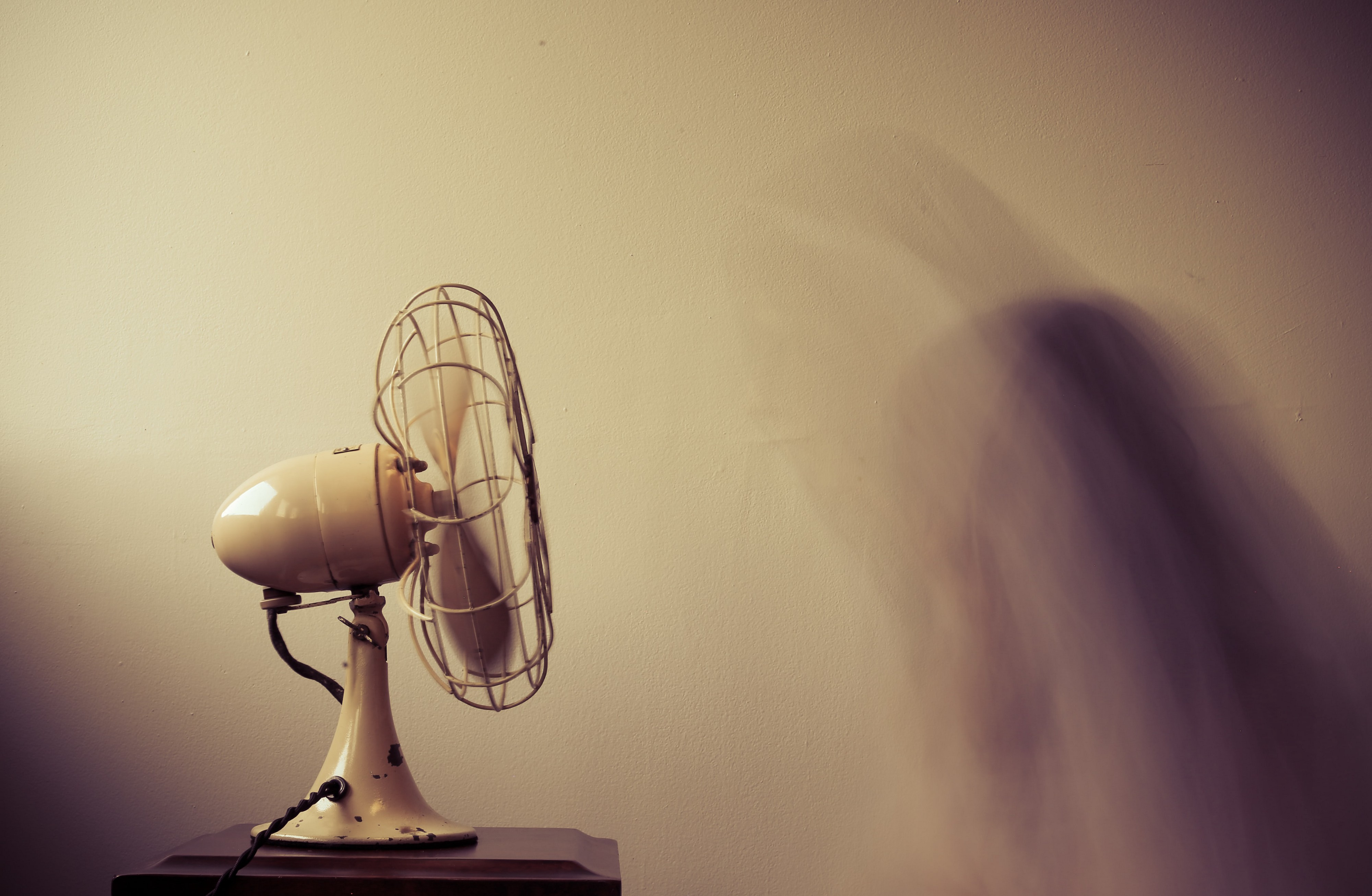 Fan blowing with a blurred image of a person.