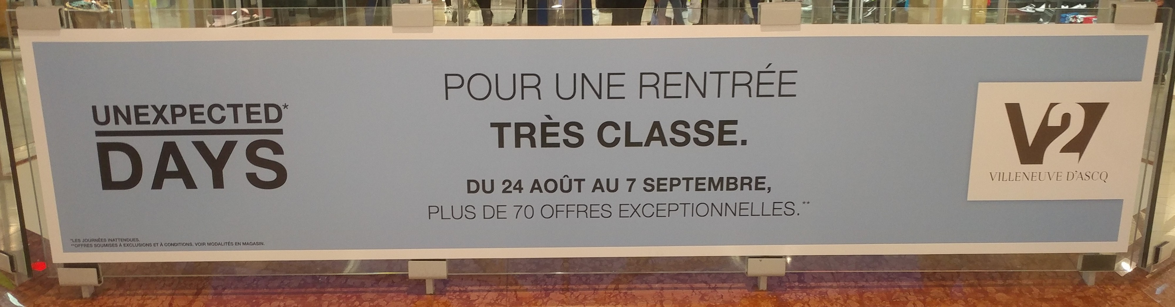 """Banner in shopping mall with slogan in English: """"Unexpected Days."""" Then, in French: """"Pour une rentrée très classe."""""""