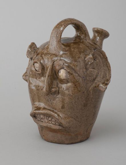 Brown ceramic face jug with an ambiguous expression.
