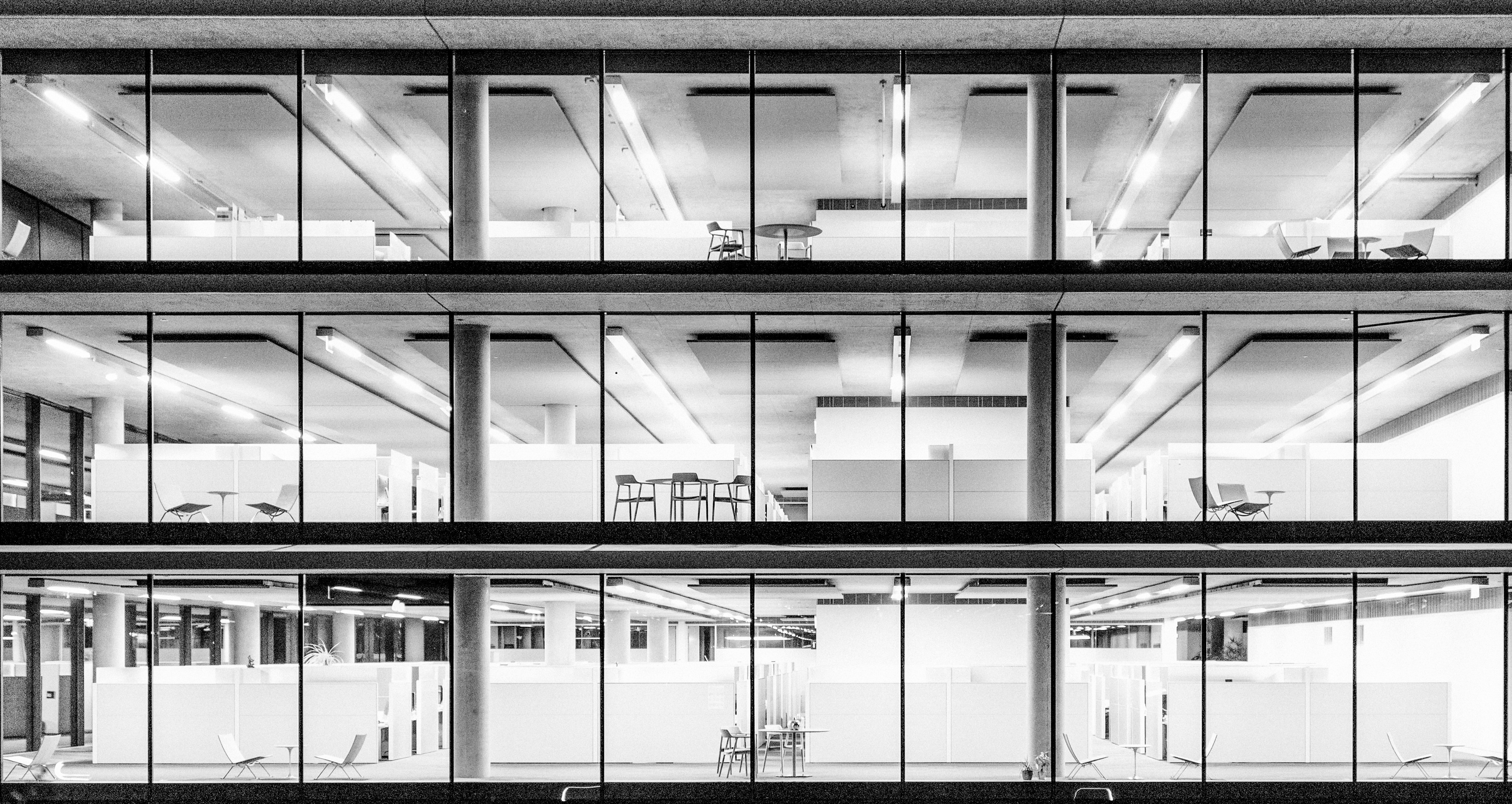 Black and White image of an unoccupied modern office space at night.