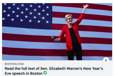 Elizabeth Warren stands, smiling, in front of an enormous American flag, a mic in her right hand, her left raised upwards.