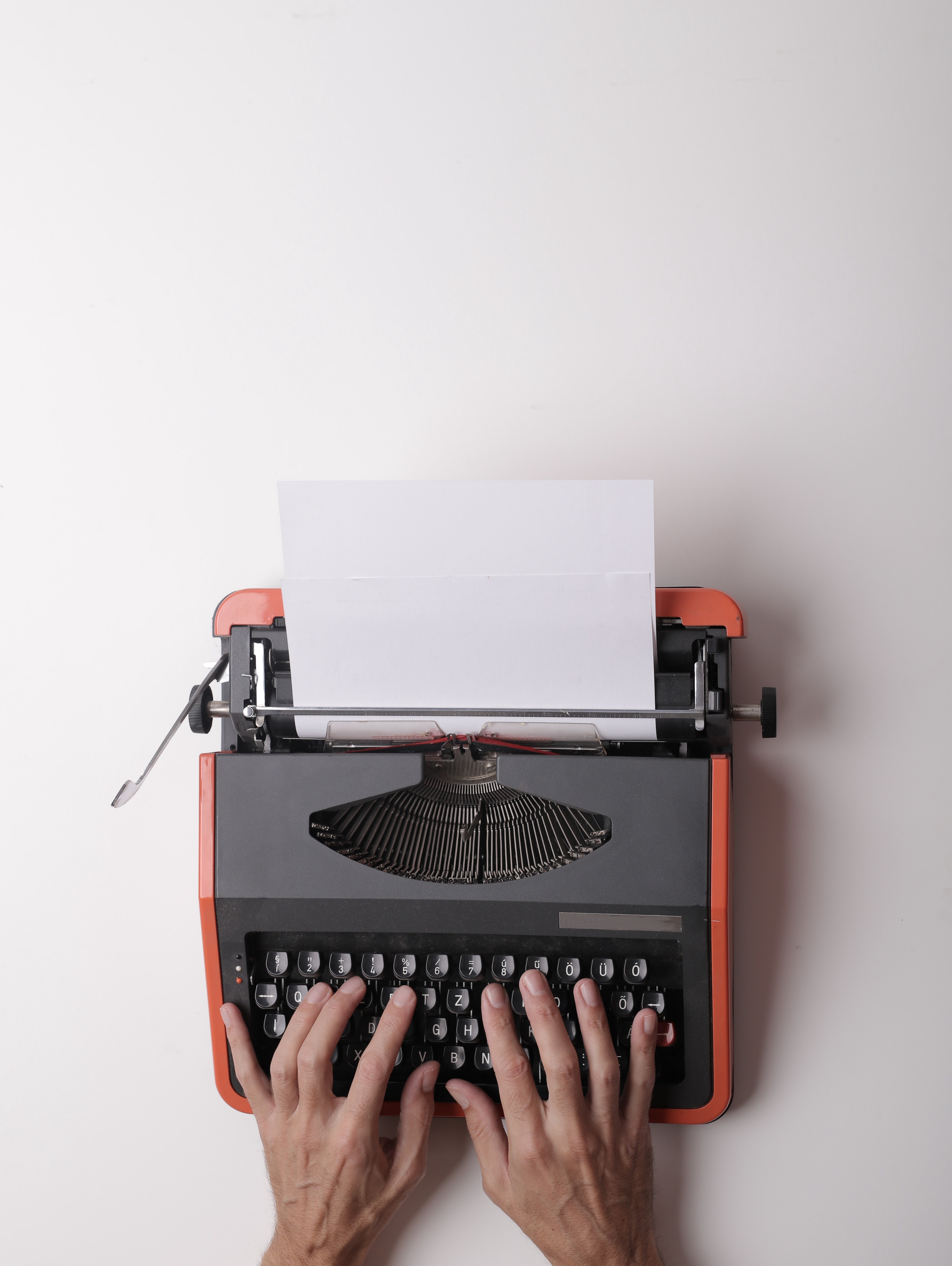 A typewritter in front of a white background with a pair of hands on top of it.