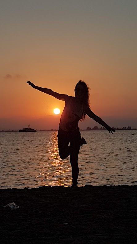 A girl in a shadow posing in a Yin Yang shirt with a sunset in the background