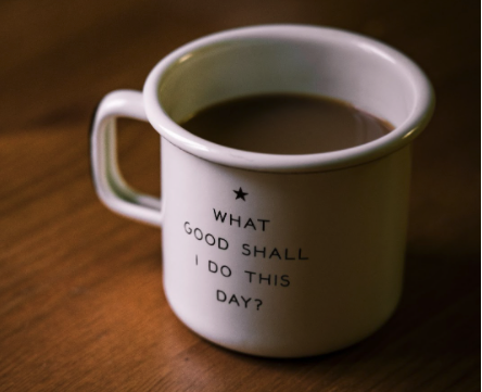 Cup of coffee with 'What good shall I do this day?' written on it