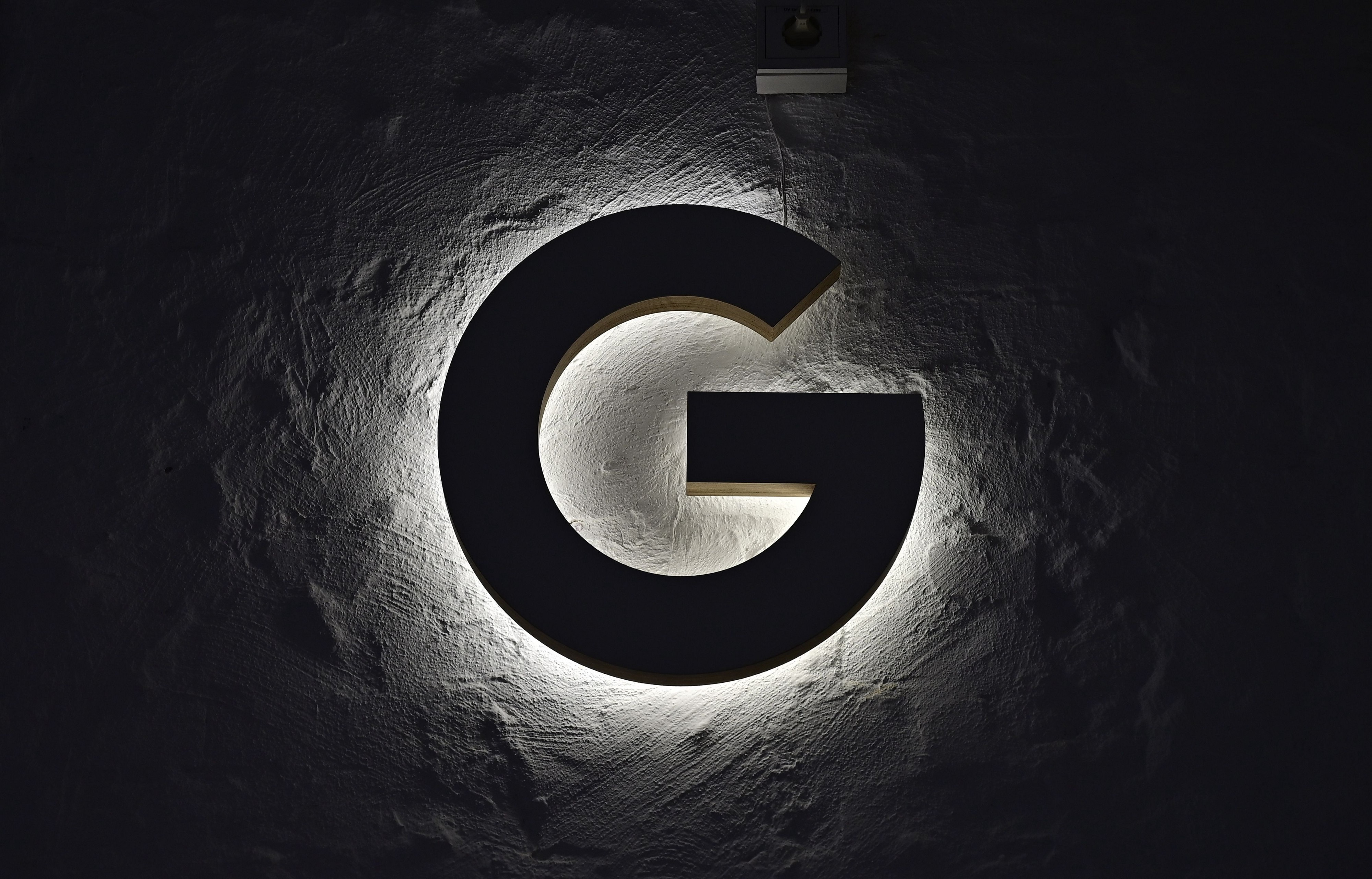 """An illuminated """"G"""" hangs on the wall."""