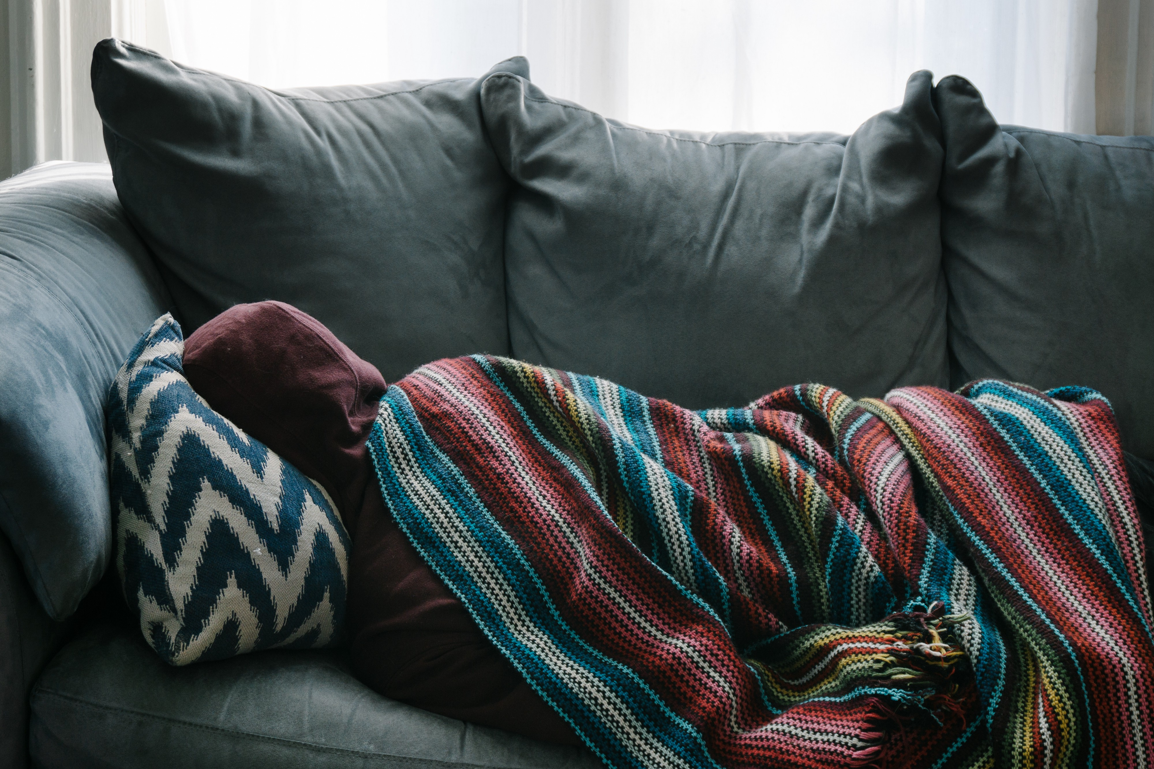 Photo of a person wearing a purple hoodie curled up on a grey couch under a striped blanket and facing away from the camera.