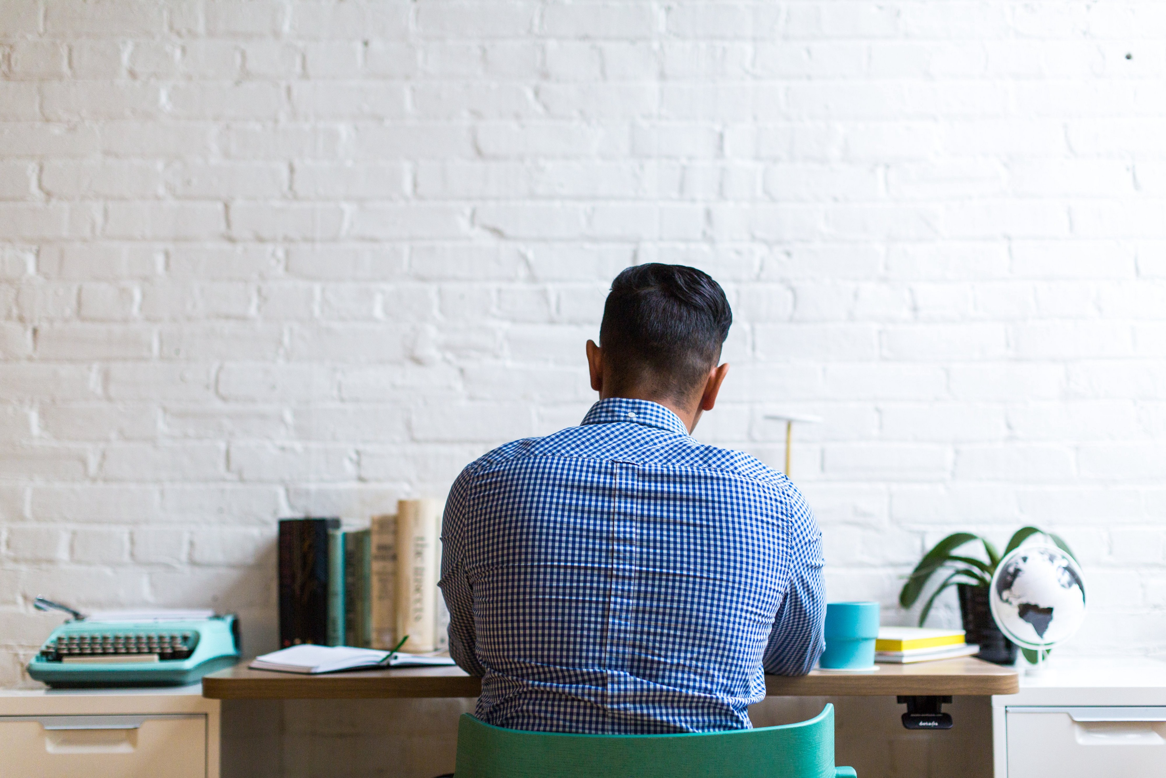 man sitting at a desk thinking and working, his back to the viewer