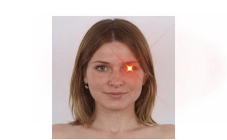 picture of a caucasian woman from the neck up. she is nude, light brown hair and there is a laser beam coming out of 1 eye