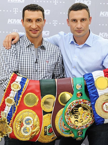 Photos shows the brothers with six title belts. Source: Photo by Wikimedia Commons user Vergo, published under Creative Commons license to the public domain, December 5, 2012, https://commons.wikimedia.org/wiki/File:VladimirVitaliy.jpg, accessed May 2020.