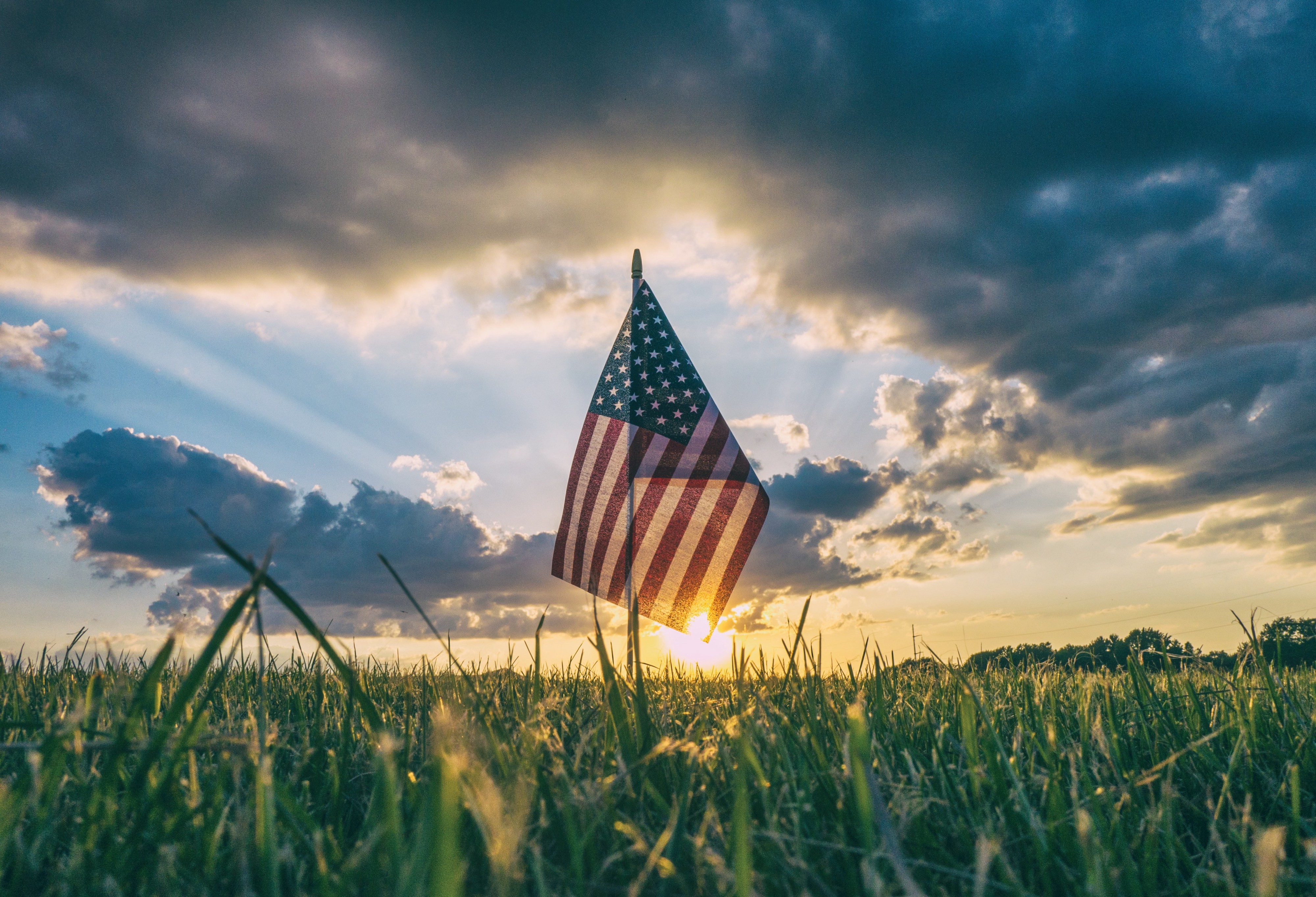 American flag in field, sun behind it, dramatic sky