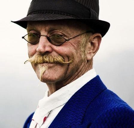 head and shoulder view of Gary in quirky hat, glasses, waxed handlebar moustache, and midnight blue suit.