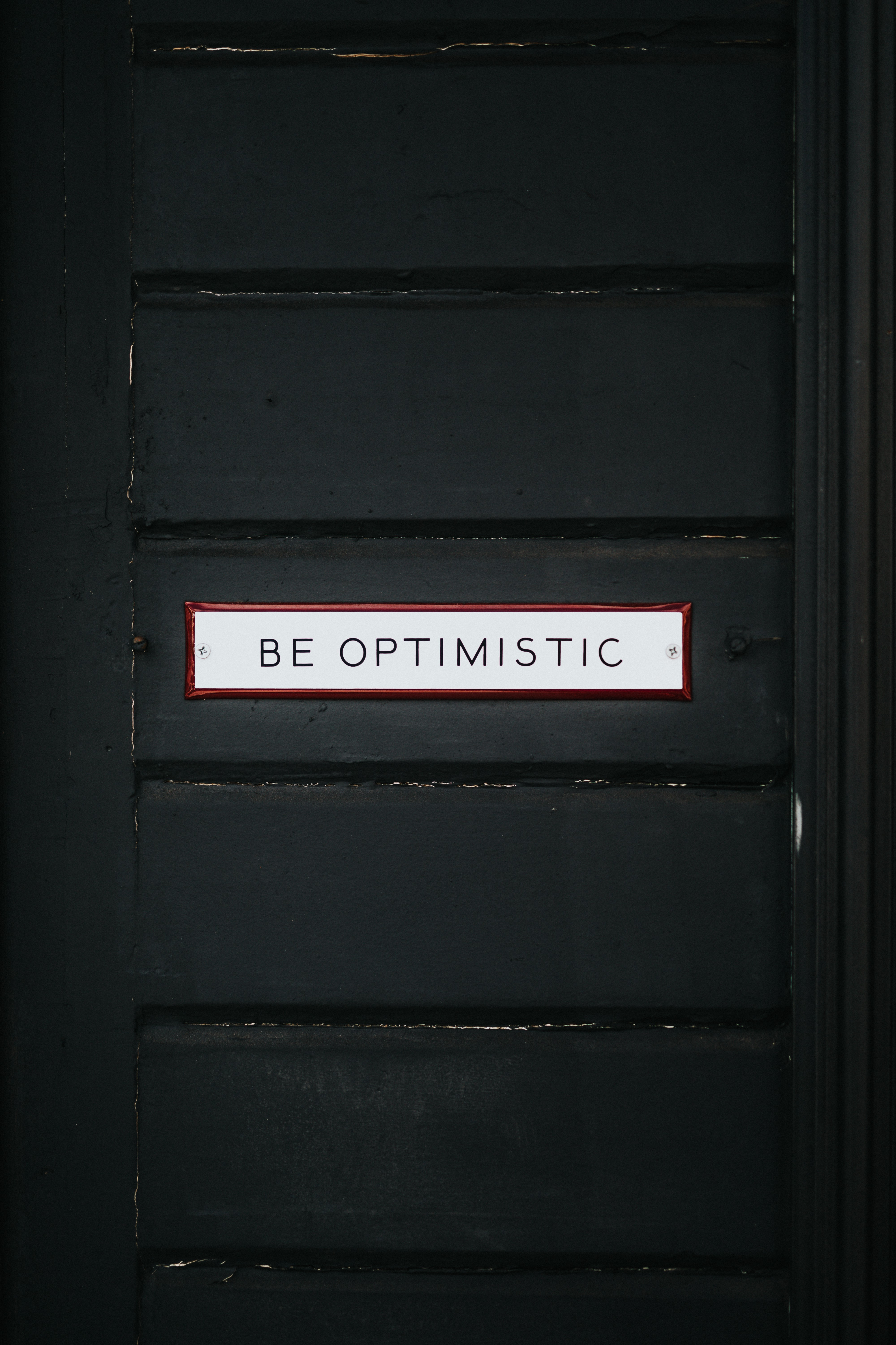 Black door with the text 'be optimistic' on it