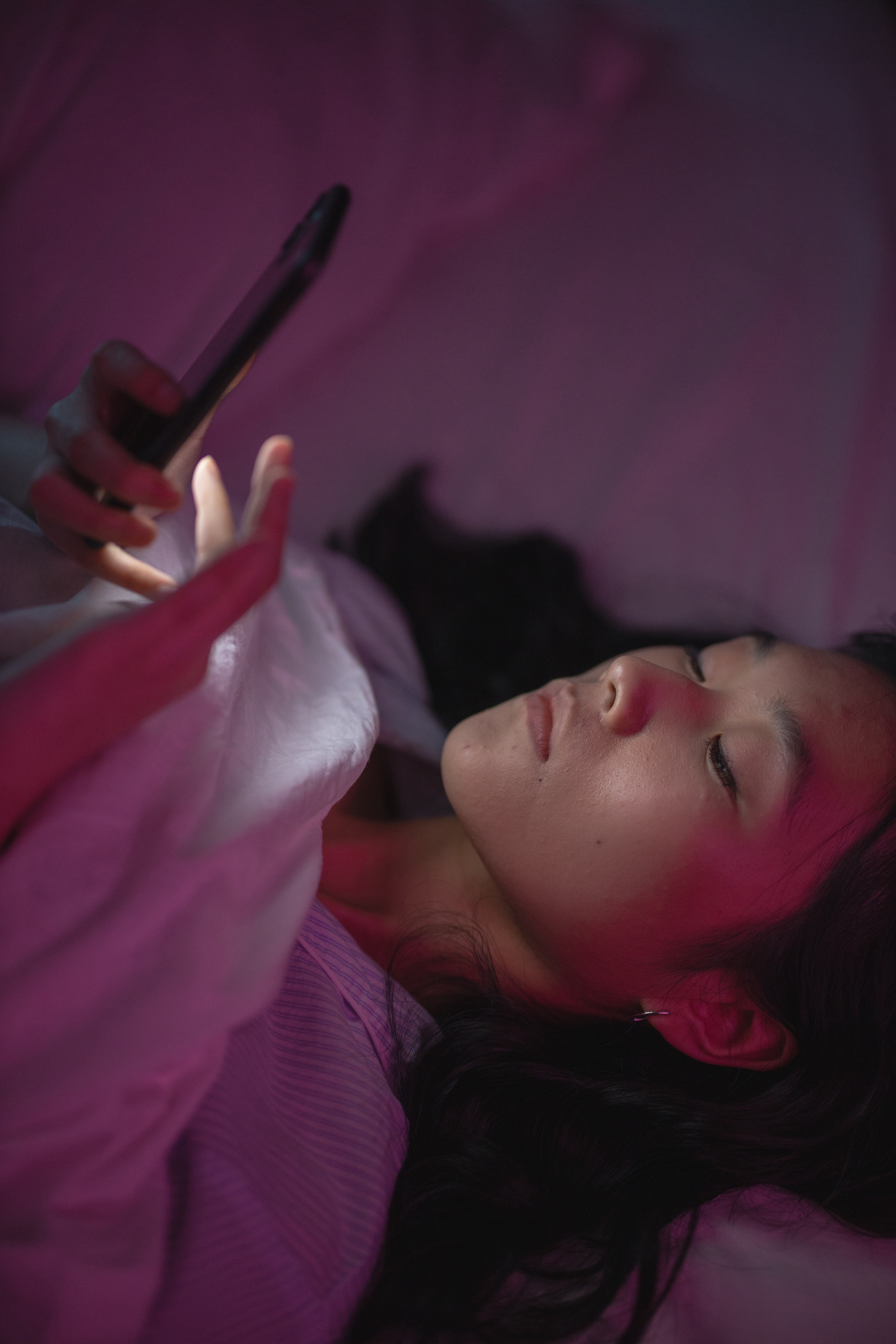 A lady uses her phone while lying down on bed at night.