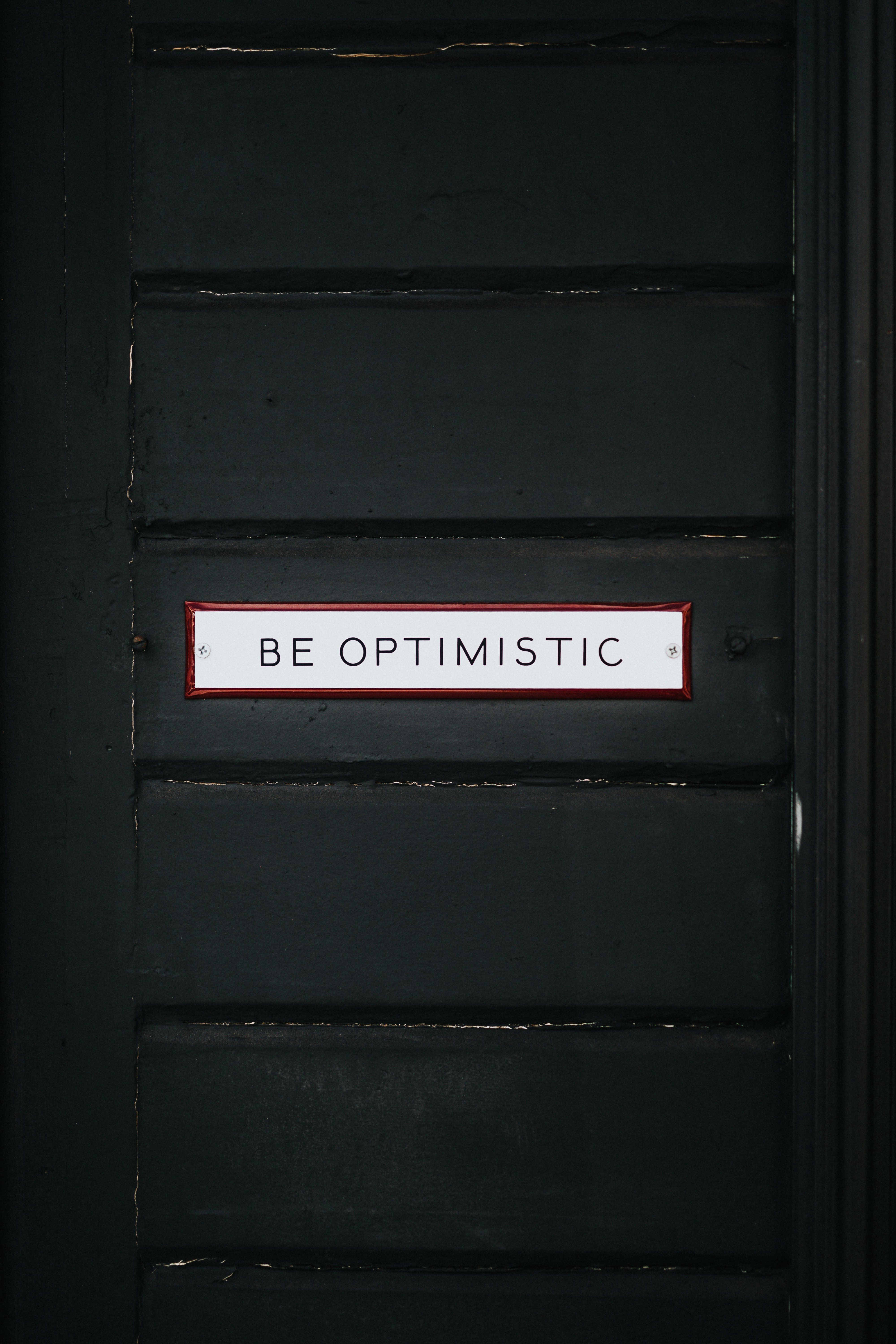 """A text written on a door that reads, """"Be Optimistic""""."""
