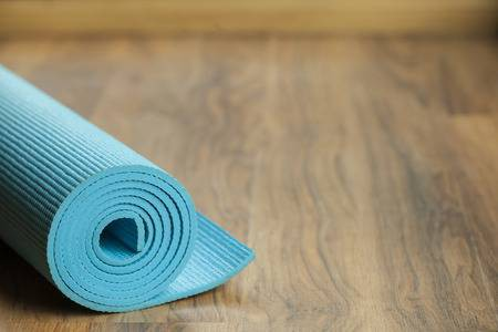 Rolled up blue yoga mat on a floor.