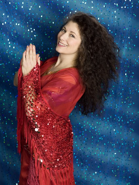 This is a photo of the author standing, smiling, hands together, in red with sparkly blue back drop