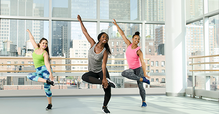 three smiling dancers in a balanced pose in a new york city studio