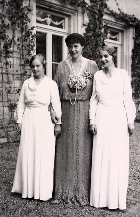 Princess Cecilie of Prussia in a floor-length dress flanked by her teenage daughters, both dressed in white.