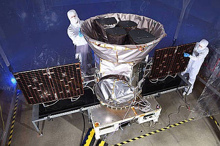 The TESS spacecraft is seen prior to launch, being serviced by a pair of technicians.