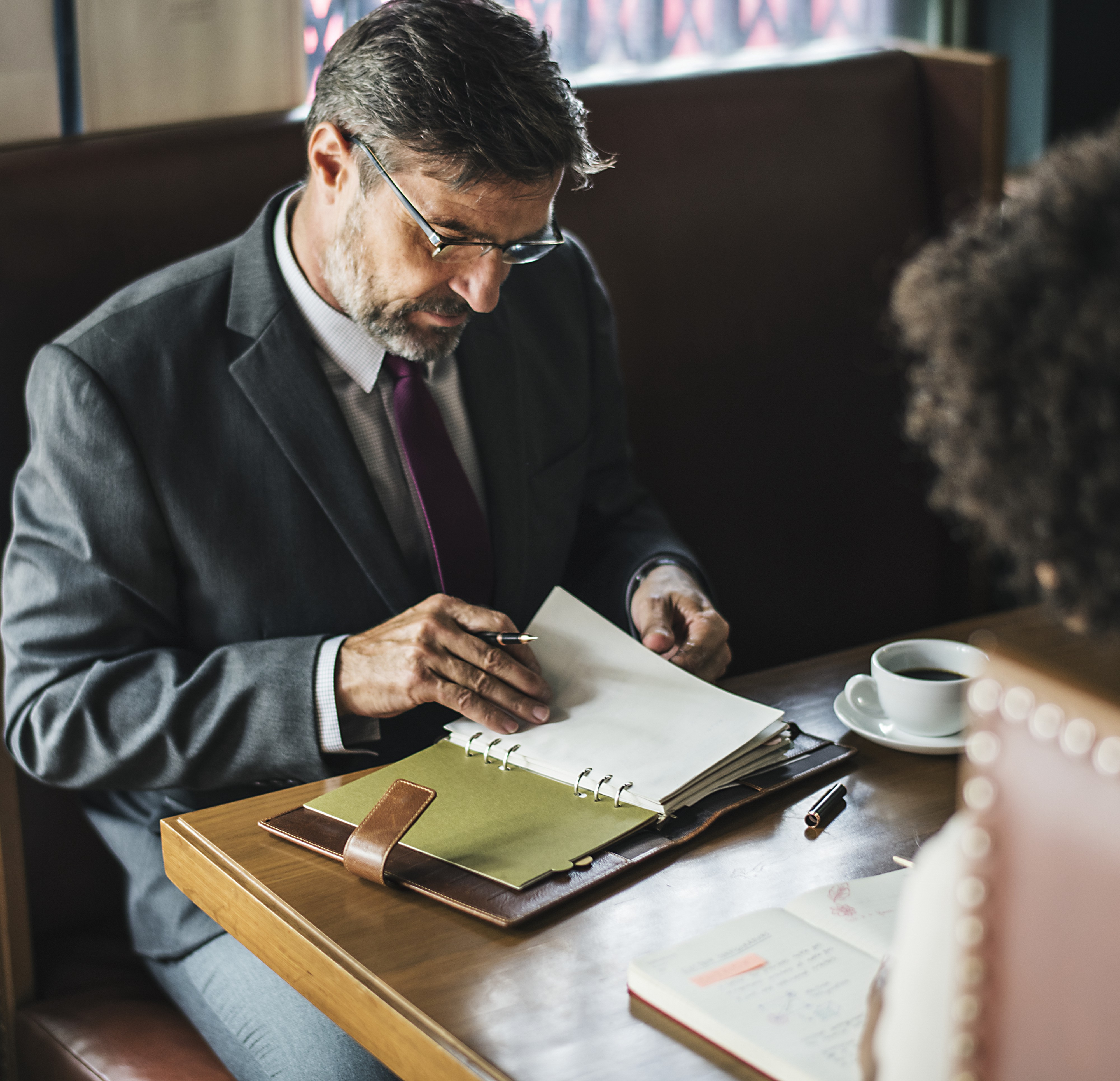 A man looking at paperwork, sitting across the table from a woman