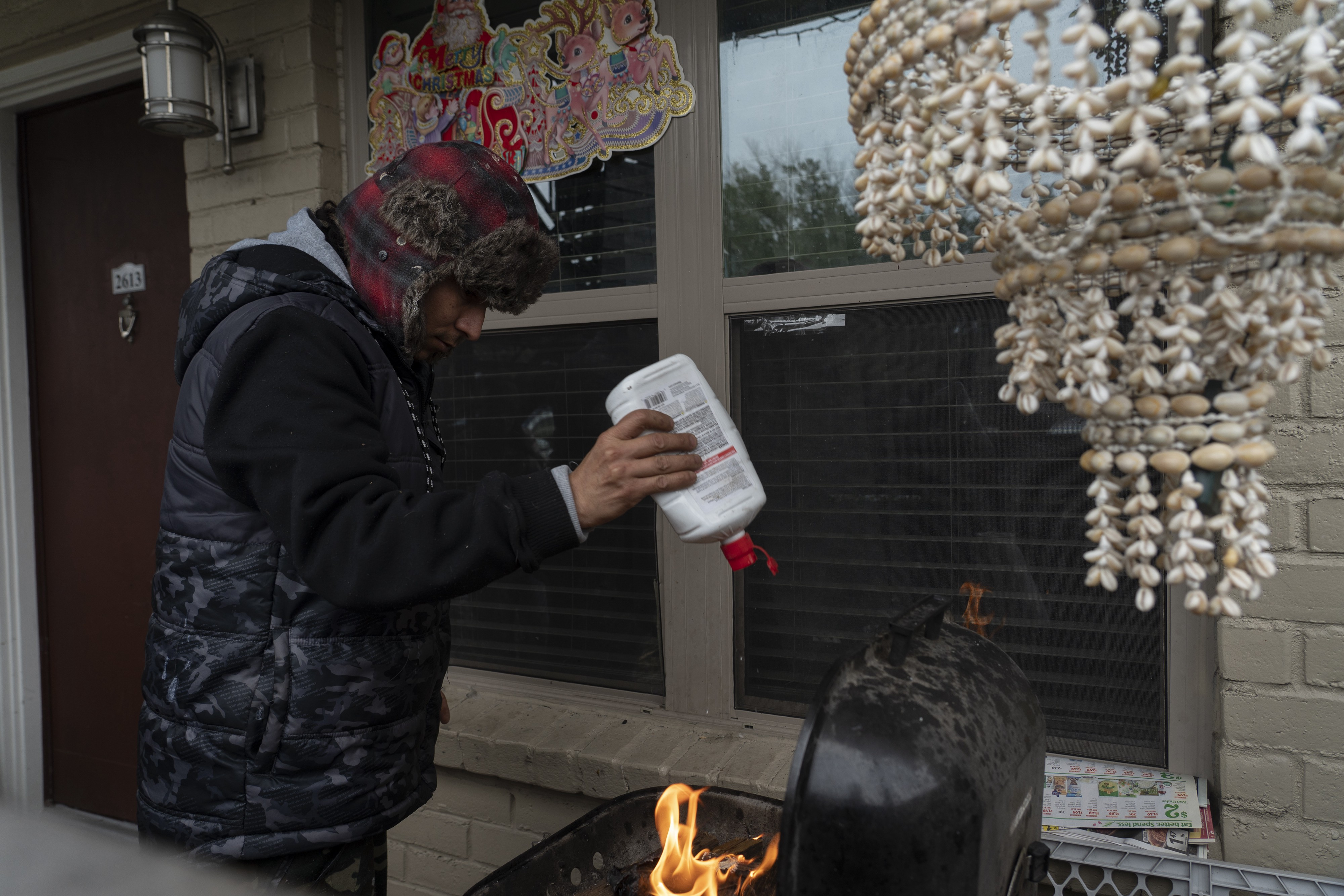 Victor Zelaya tries to start a fire on a barbecue grill during power outage caused by the winter storm on February 16, 2021 in Houston, Texas