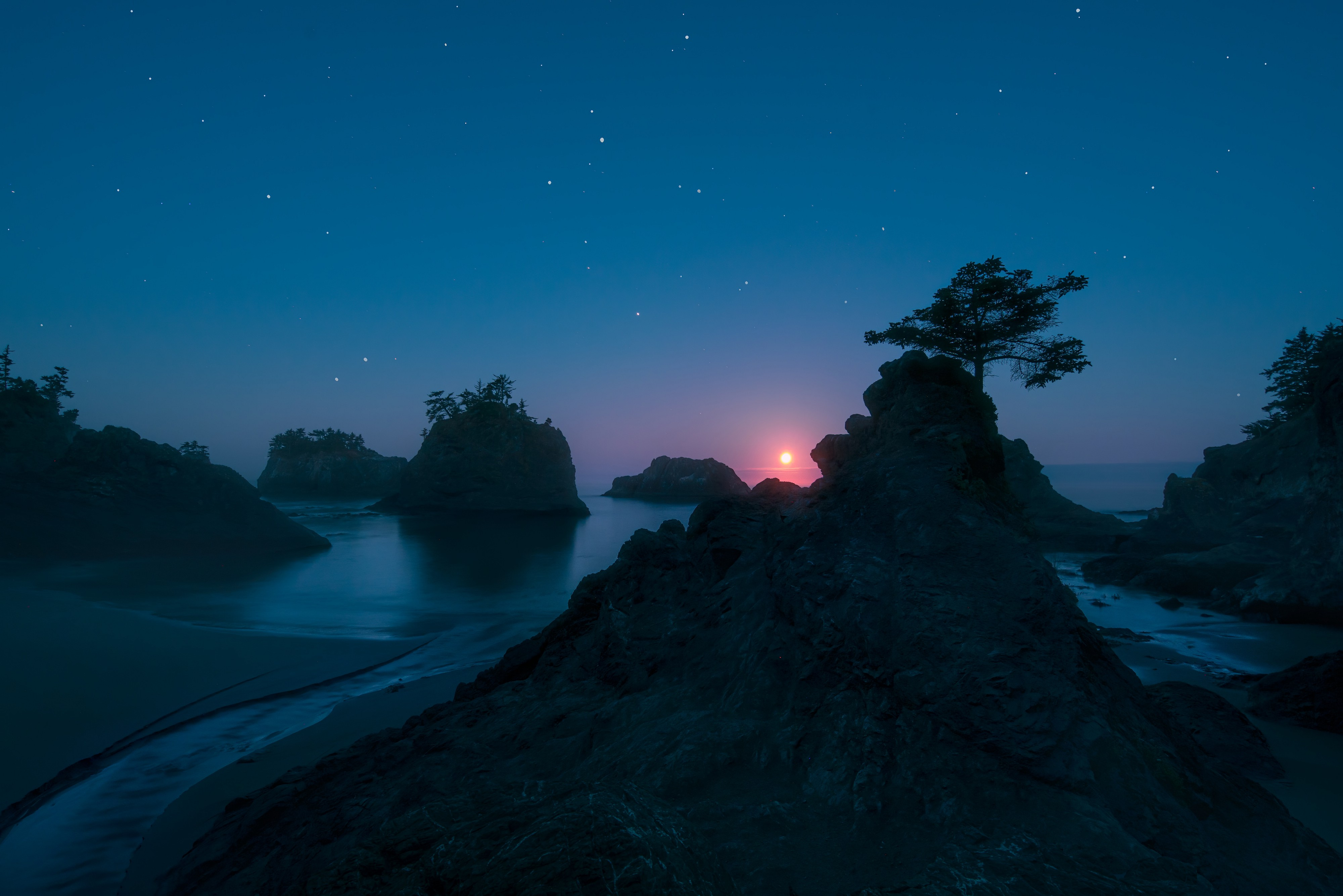 Fine art photograph of a pink moon peeking out over rock structures, trees, and water, all in deep blue