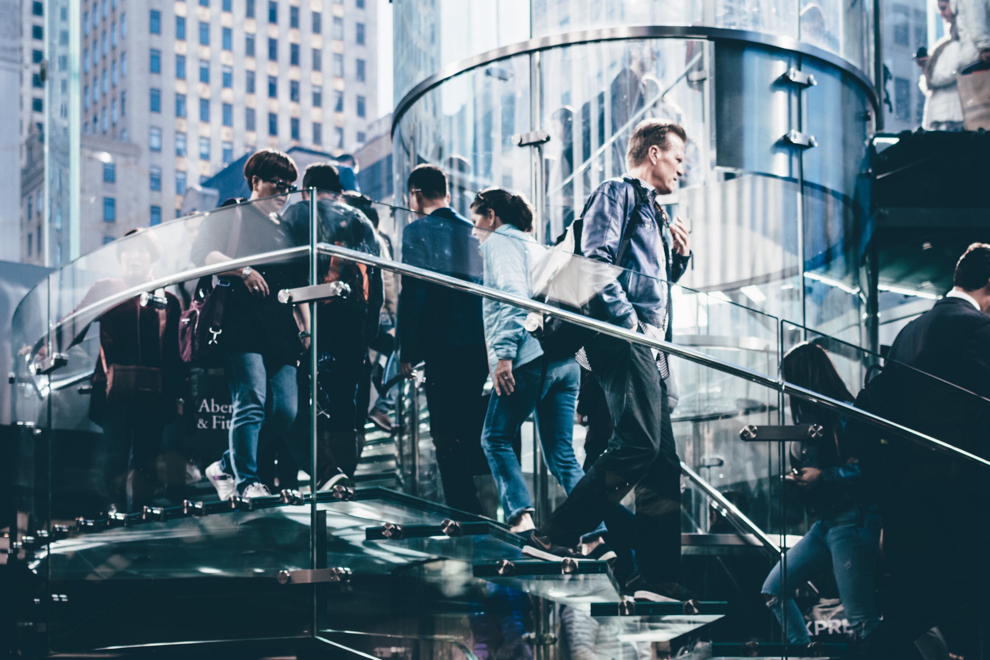 People walking on outside glass staircase in city surrounded by tall buildings