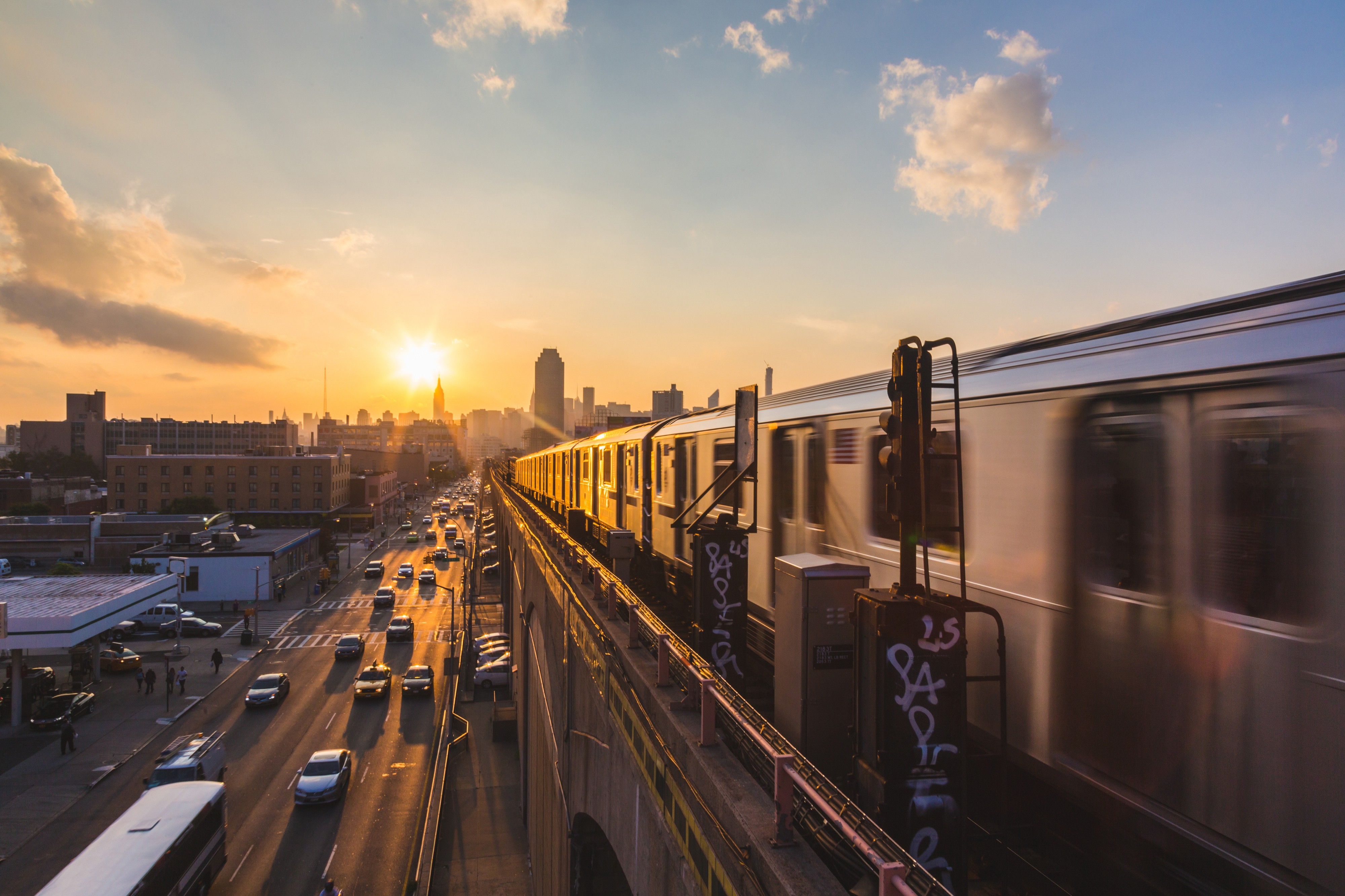 An elevated train rides through New York City at sunset.