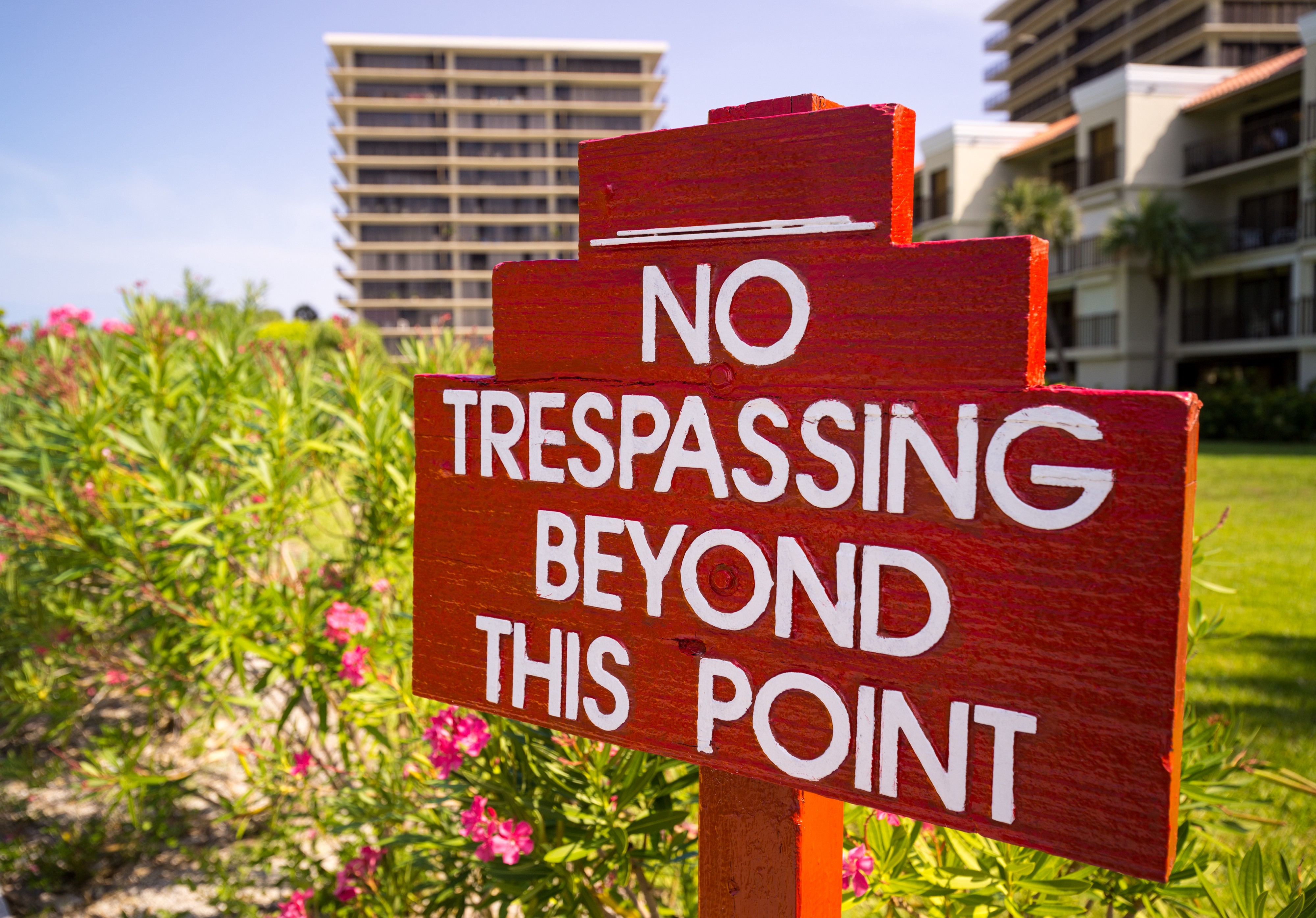 """Red sign with white print on grass in front of tall buildings """"no trespassing beyond this point"""""""