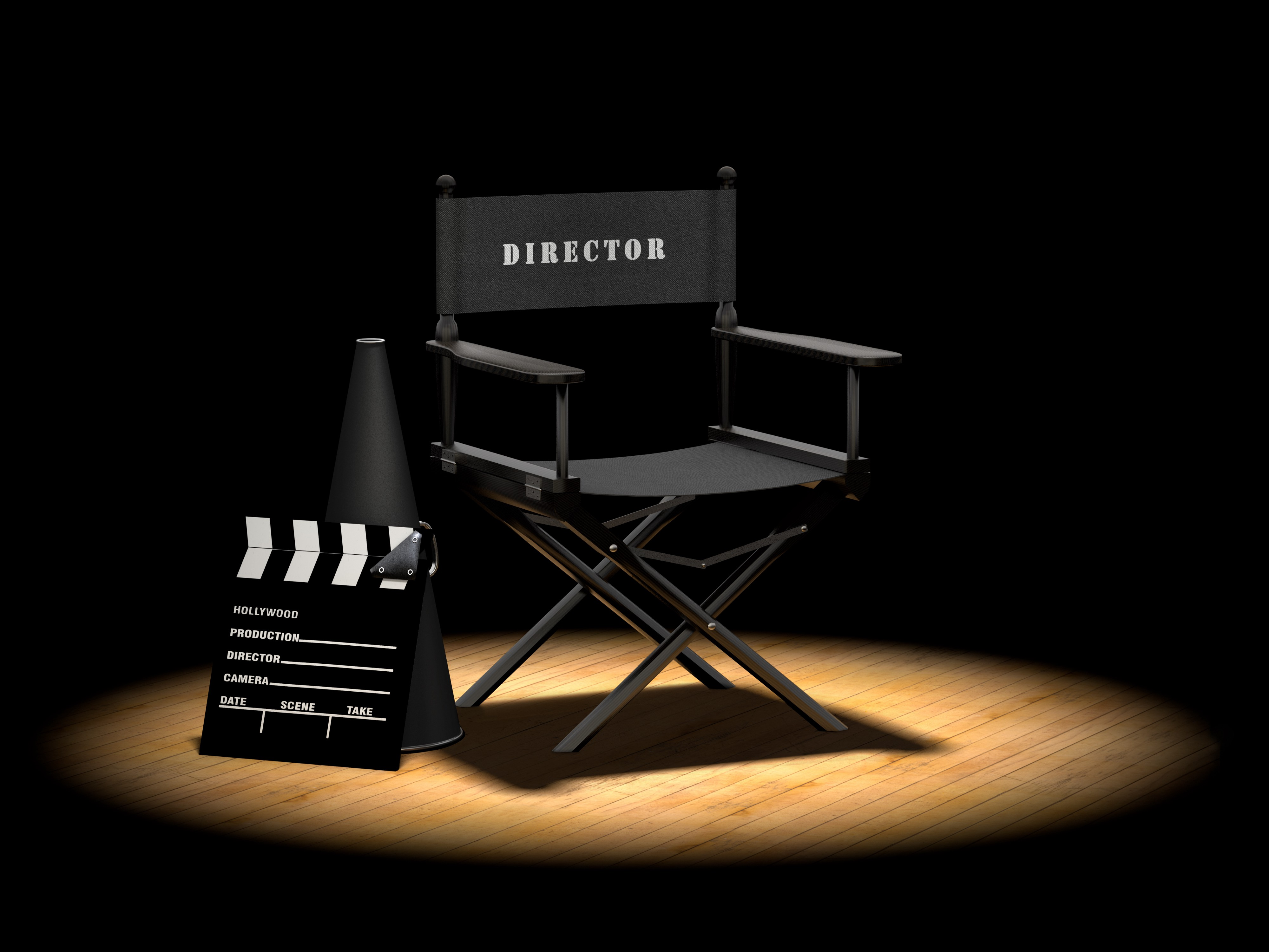 Black directors chair, camera slate, and megaphone in a spotlight on a wooden floor