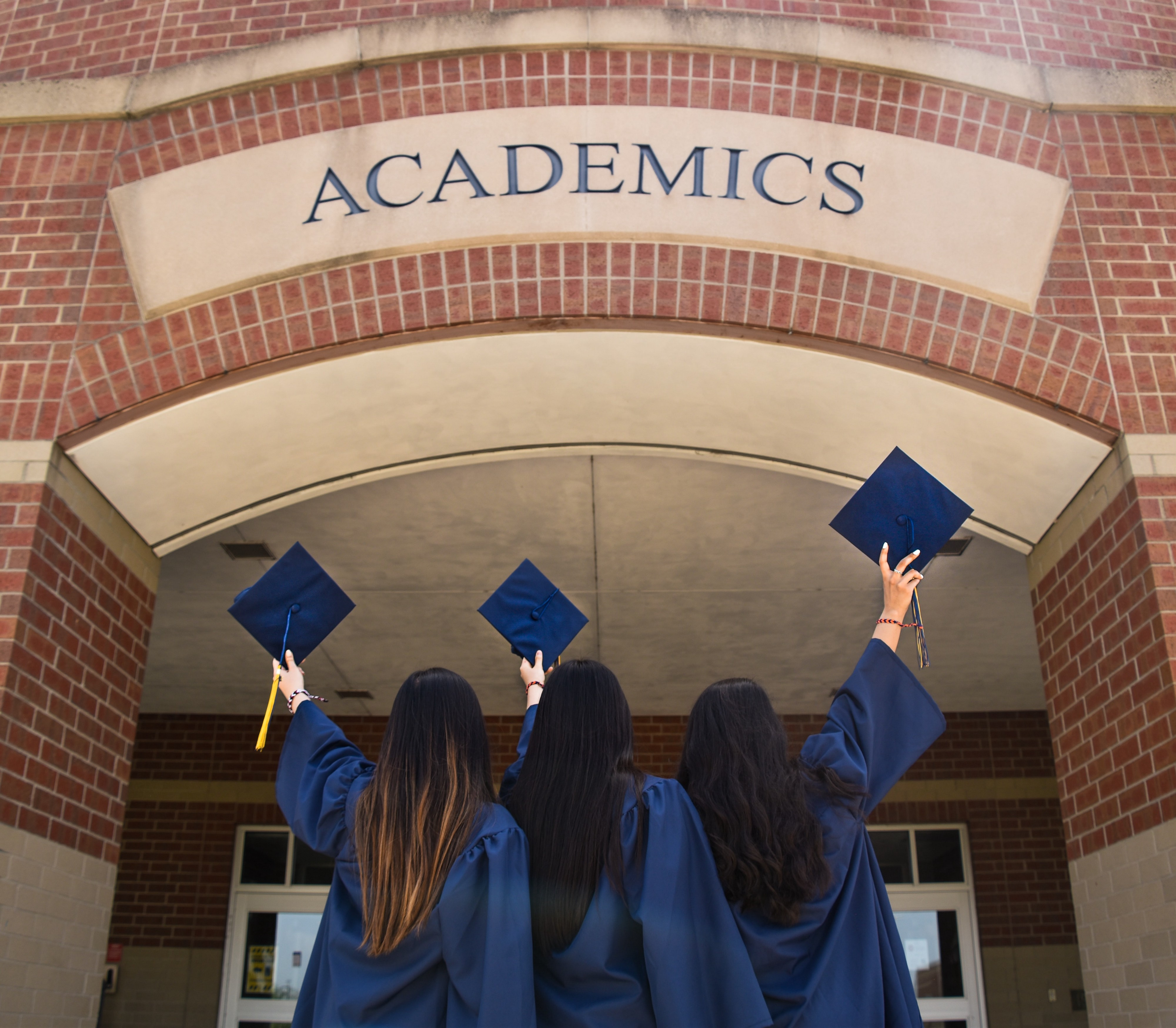 Three young women in graduation robes hold their caps up high.