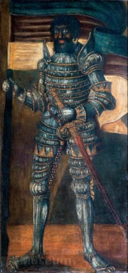 A bearded Black man stands in full armor. His left arm rests on his belted sword; he carries a flag in his right hand.