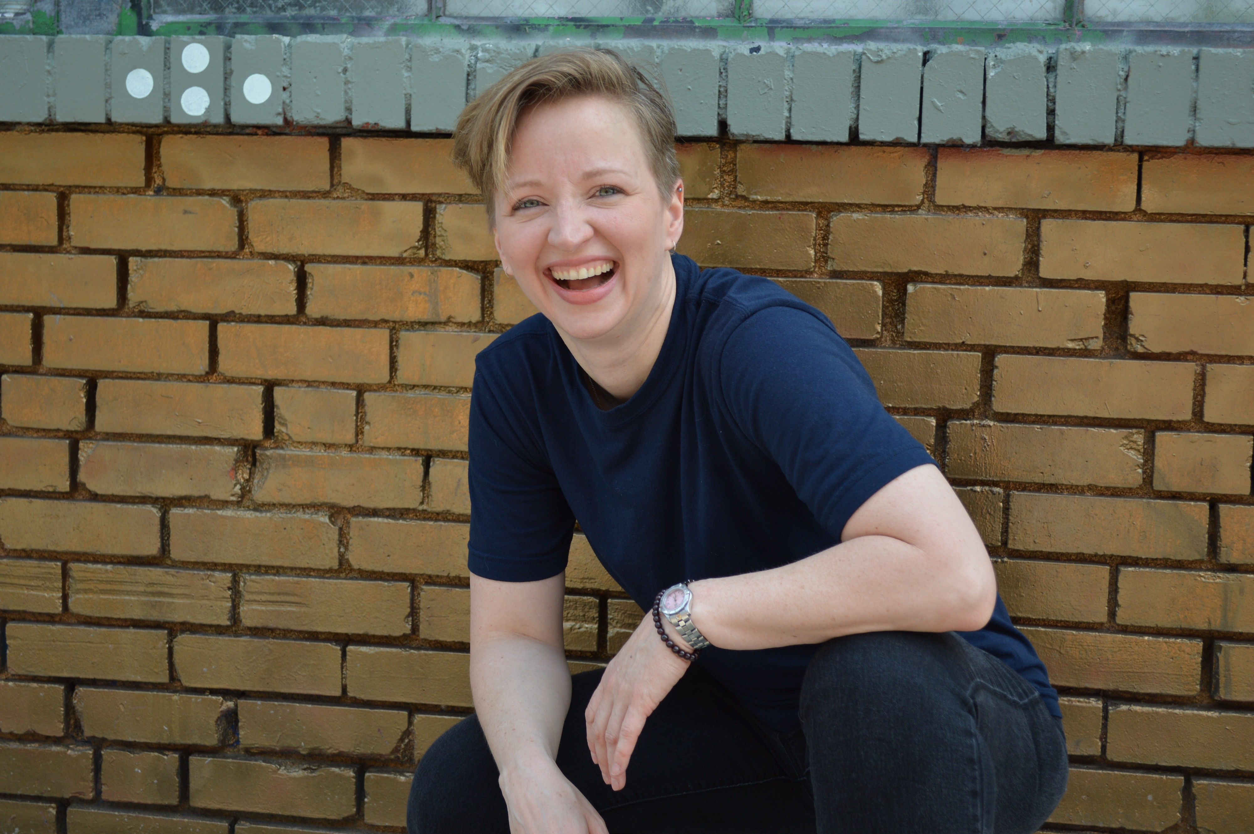 Diane Whiddon laughing, crouched in front of brick wall