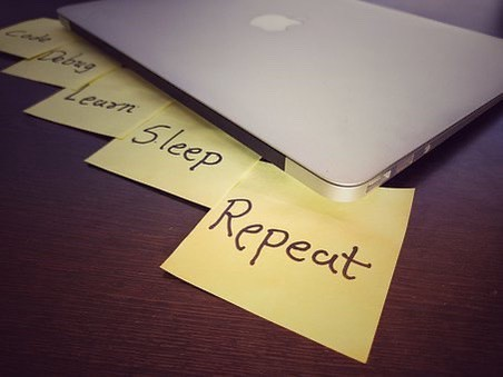 """A laptop with sticky notes reading """"Code"""", """"Debug"""", """"Learn"""", """"Sleep"""", """"Repeat"""""""