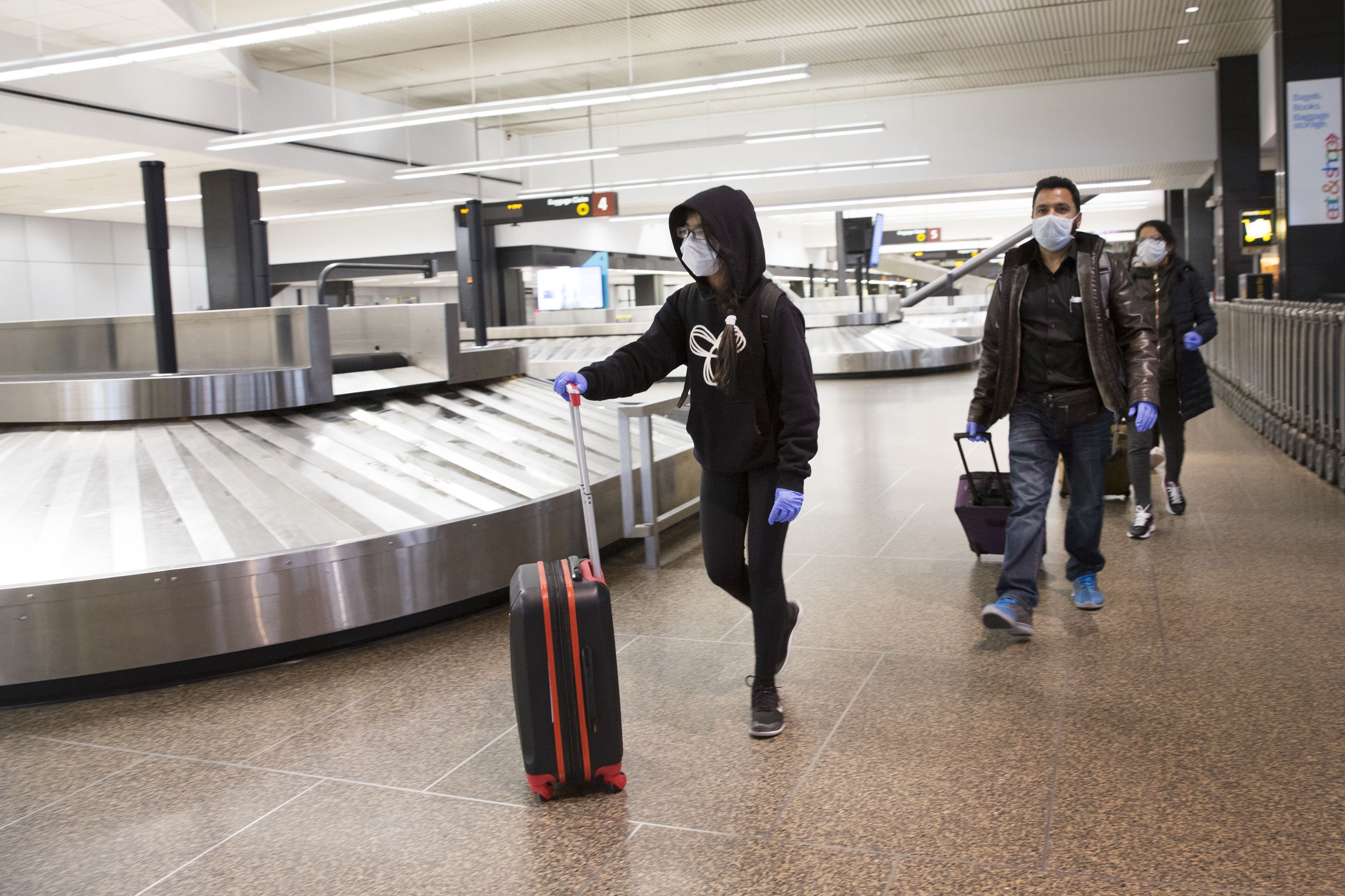 Sukhneet Dhillon, age 11, and family wear masks as they arrive from a flight from India, through Tokyo, to Sea-Tac airport.