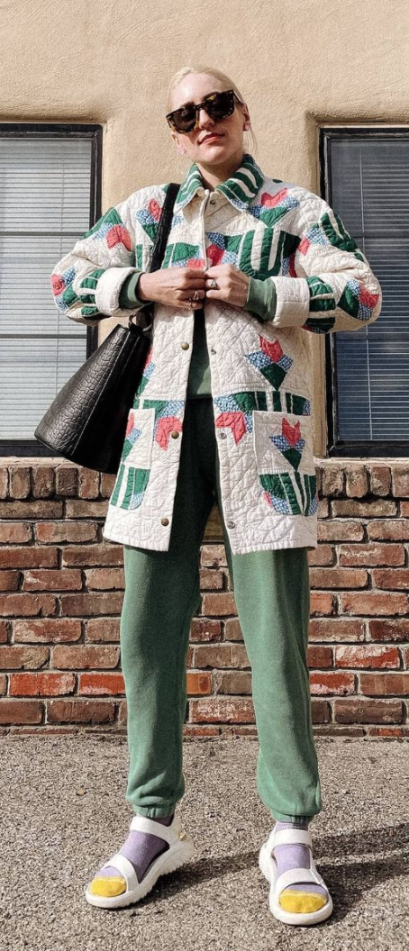 A woman wearing a vintage quilted jacket with a quaint motif and faded green sweatpants in a very stylish and confident way.