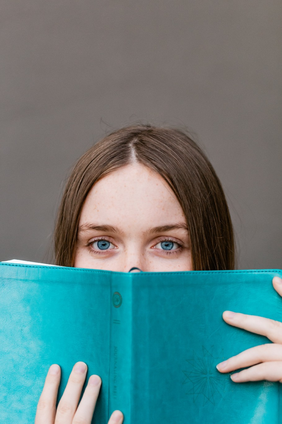 Woman holding an open book close to her face.