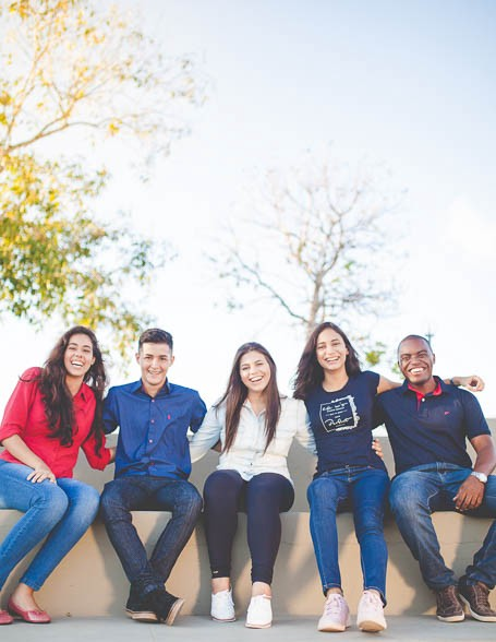 Five friends sitting on a bench with arms around each other