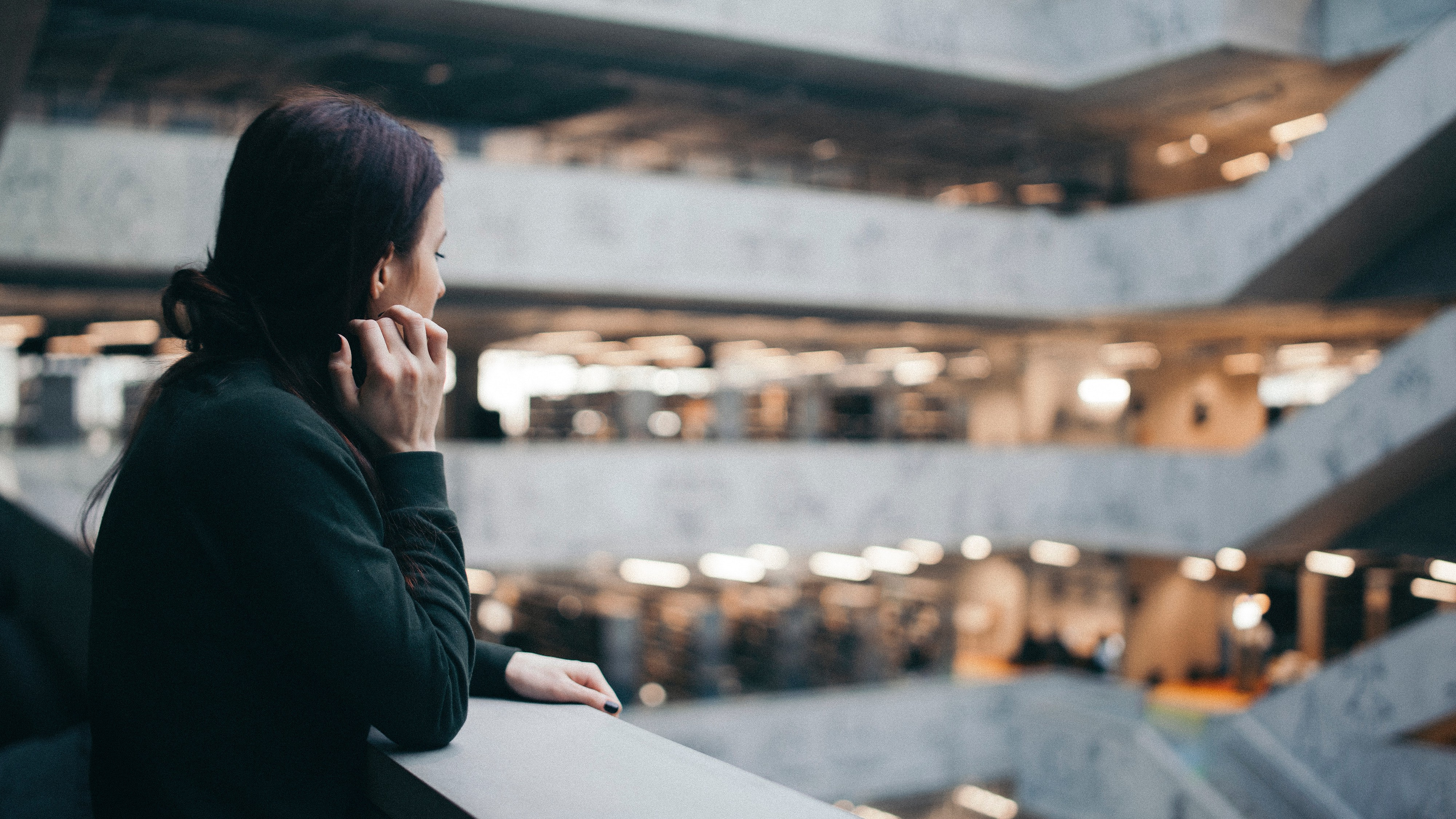 Woman looking out over the atrium of a building